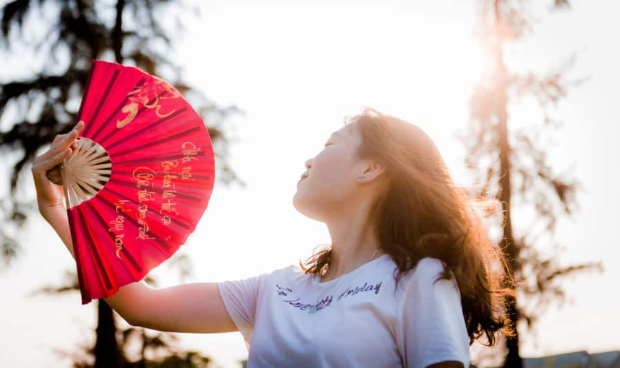 Chinese Fans - close up photo of woman holding red hand fan